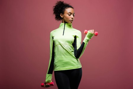 Photo pour Belle sportive afro-américain de formation avec des haltères isolés sur brown - image libre de droit