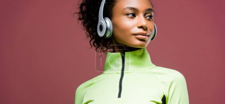 Photo for Panoramic shot of beautiful african american sportswoman in headphones isolated on brown with copy space - Royalty Free Image