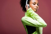 attractive african american sportswoman in headphones looking at camera isolated on brown with copy space