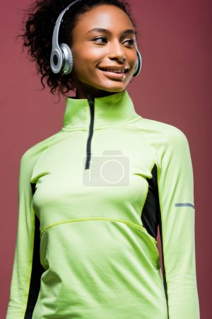 Photo for Beautiful smiling african american sportswoman in headphones and track jacket isolated on brown - Royalty Free Image