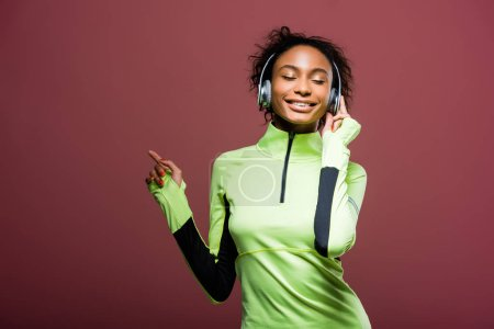 Photo for Beautiful smiling african american sportswoman in headphones listening music with eyes closed isolated on brown - Royalty Free Image