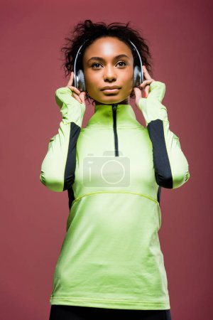 Photo for Beautiful african american sportswoman in headphones and track jacket isolated on brown - Royalty Free Image
