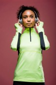 beautiful african american sportswoman in headphones and track jacket isolated on brown