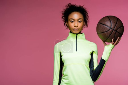 Photo for Beautiful african american sportswoman looking at camera and holding basketball isolated on pink with copy space - Royalty Free Image
