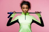 beautiful african american sportswoman looking at camera while posing with skipping rope isolated on pink
