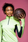 beautiful smiling african american sportswoman holding basketball isolated on pink