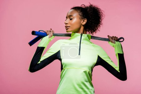 Photo for Beautiful african american sportswoman posing with skipping rope isolated on pink - Royalty Free Image