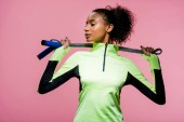 beautiful african american sportswoman posing with skipping rope isolated on pink