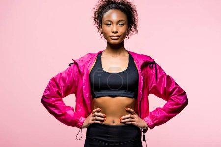 Foto de Atractivo deportista afroamericana en Cazadora mirando a cámara y posar con manos akimbo aisladas en rosa - Imagen libre de derechos
