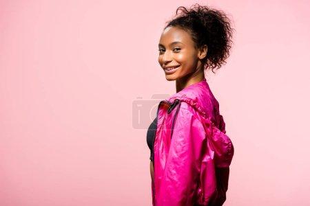 Photo pour Séduisante sportive afro-américaine en coupe-vent en regardant la caméra et souriant isolés sur rose avec espace copie - image libre de droit