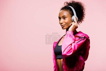 Foto de Hermosa deportista afroamericana en auriculares mirando lejos aislada en rosa con espacio de copia - Imagen libre de derechos