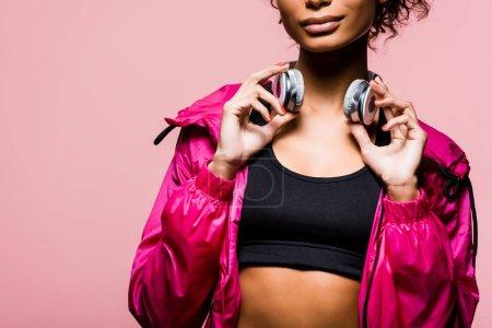 Photo pour Vue partielle de l'athlète afro-américain en coupe-vent avec casque isolé sur rose avec espace copie - image libre de droit
