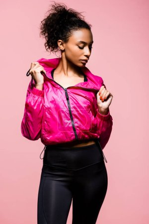 Foto de Atractivo deportista afroamericana en Cazadora posando aislada en rosa - Imagen libre de derechos
