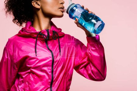 Photo for Cropped view of african american sportswoman drinking water from sport bottle isolated on pink - Royalty Free Image