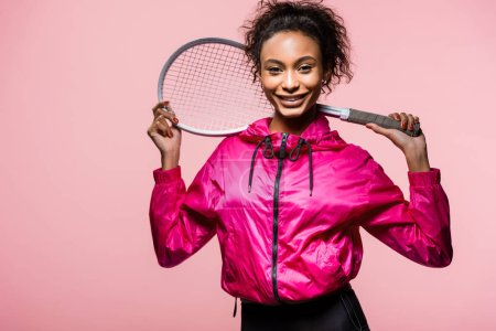 Photo for Beautiful african american sportswoman holding tennis racket, looking at camera and smiling isolated on pink - Royalty Free Image