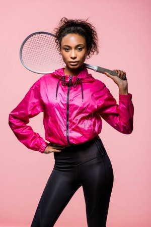 Photo for Beautiful african american sportswoman holding tennis racket and looking at camera isolated on pink - Royalty Free Image