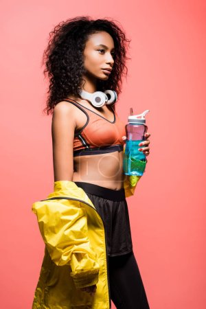 Photo for Beautiful african american sportswoman posing with headphones and sport bottle isolated on coral - Royalty Free Image