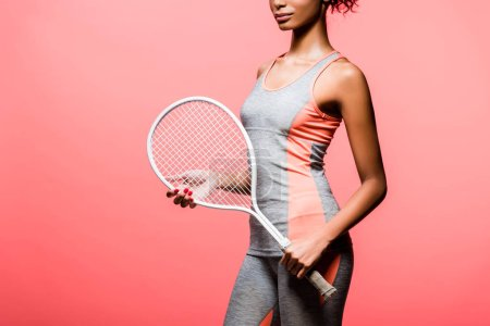 Photo for Cropped view of african american sportswoman holding tennis racket isolated on coral with copy space - Royalty Free Image