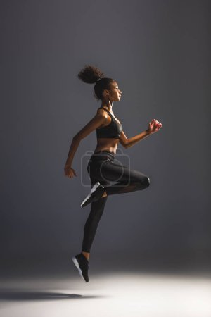 Photo for Side view of beautiful athletic african american sportswoman jumping on black - Royalty Free Image