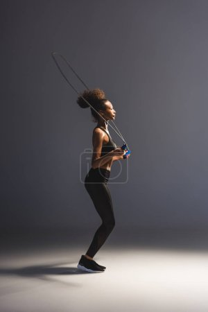 Photo for Athletic african american sportswoman exercising with skipping rope on grey - Royalty Free Image