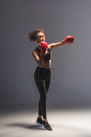 Photo for Beautiful athletic african american sportswoman boxing on black - Royalty Free Image