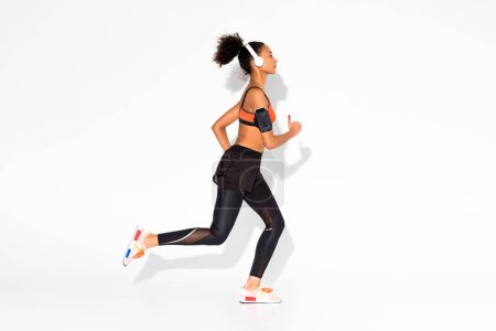 Photo for Athletic african american sportswoman with headphones and smartphone armband running on white - Royalty Free Image