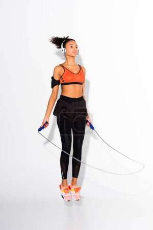 Photo for Athletic african american sportswoman in headphones exercising with skipping rope on white - Royalty Free Image
