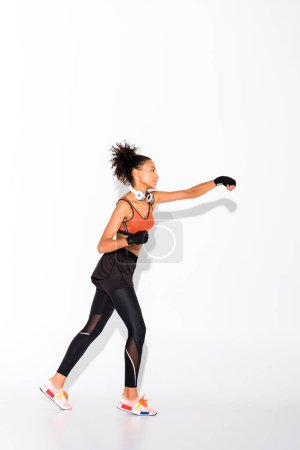 Photo for Athletic african american sportswoman with headphones training in sport gloves on white - Royalty Free Image