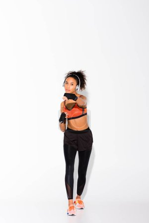 Photo for Athletic african american sportswoman looking at camera and training in sport gloves on white - Royalty Free Image
