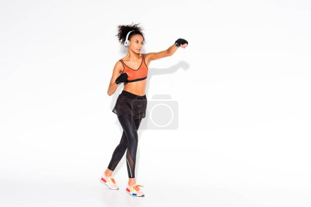 Photo for Athletic african american sportswoman training in sport gloves on white with copy space - Royalty Free Image