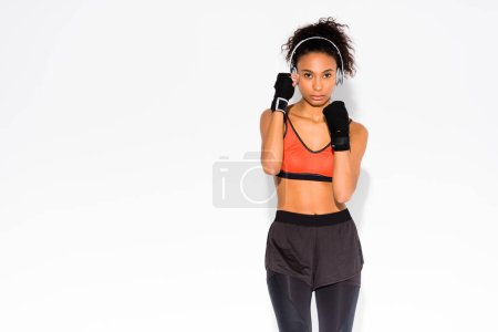 Photo for Beautiful athletic african american sportswoman in sport gloves looking at camera on white with copy space - Royalty Free Image