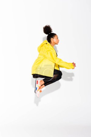 Photo for Side view of athletic african american sportswoman jumping on white - Royalty Free Image