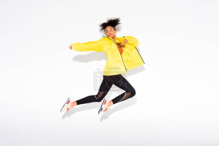 Photo for Athletic african american sportswoman jumping on white with copy space - Royalty Free Image