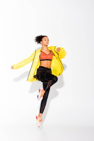 Photo for Athletic african american sportswoman in yellow sports jacket jumping on white - Royalty Free Image