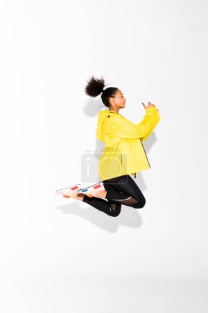 Photo for Side view of beautiful athletic african american sportswoman jumping on white - Royalty Free Image