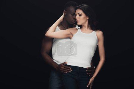 Foto de Hombre afroamericano apasionado abrazando hermosa mujer aislada en negro - Imagen libre de derechos