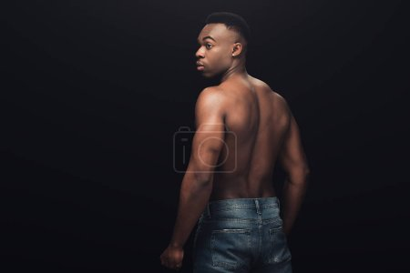 Photo for Back view of sexy muscular african american man in denim posing isolated on black with copy space - Royalty Free Image