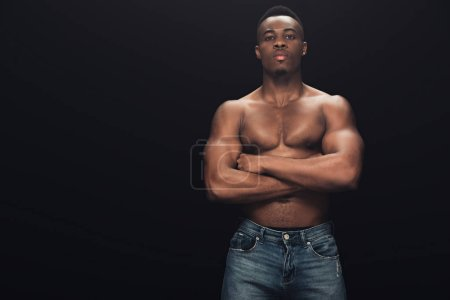 Photo for Sexy muscular african american man in denim with crossed arms looking at camera isolated on black - Royalty Free Image