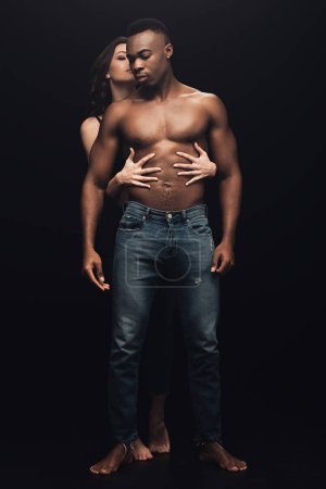 Photo for Beautiful sexy woman hugging shirtless african american man in denim isolated on black - Royalty Free Image