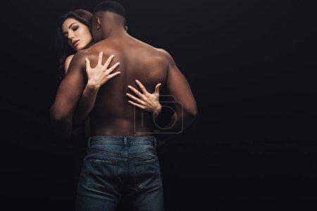 Photo pour Vue arrière de belle femme sexy étreignant torse nu homme afro-américain isolé sur noir - image libre de droit