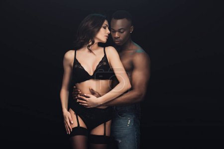 Photo for Shirtless african american man hugging sexy woman in lingerie isolated on black with copy space - Royalty Free Image