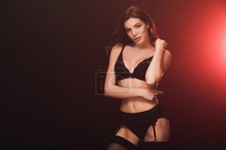 Photo pour Belle femme sexy dans la lingerie de lacet regardant l'appareil-photo sur le noir avec la lumière rouge et l'espace de copie - image libre de droit