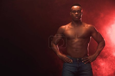 Photo for Sexy muscular african american man in denim looking at camera on dark with red light and copy space - Royalty Free Image