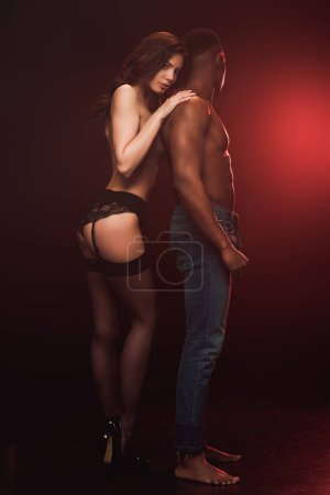 Photo for Beautiful topless woman in lingerie posing near african american man on dark with red light - Royalty Free Image