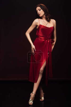 Photo for Beautiful sensual woman in red dress posing with eyes closed isolated on black - Royalty Free Image