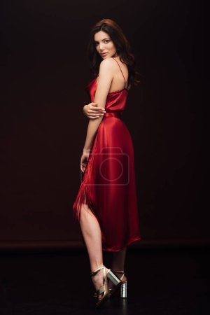 Photo for Beautiful sensual woman in red dress posing and looking at camera isolated on black - Royalty Free Image