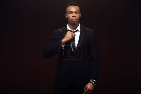 handsome african american man in suit adjusting tie and looking at camera isolated on black