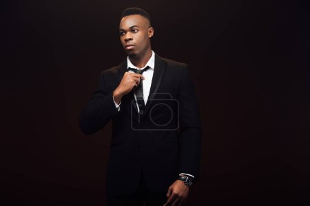 Photo for Handsome fashionable african american man in suit adjusting tie isolated on black - Royalty Free Image
