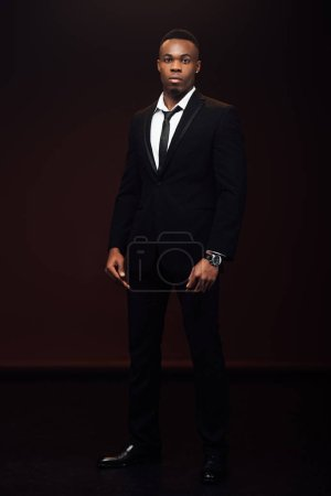 handsome fashionable african american man in suit looking at camera isolated on black