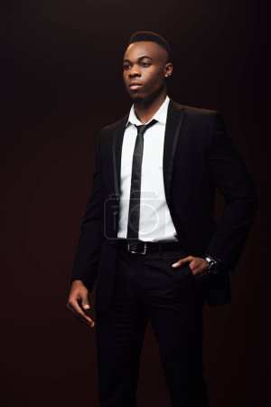 Photo for Handsome fashionable african american man in suit looking away isolated on black - Royalty Free Image
